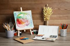 Easel with abstract painting and set of professional art. Supplies on table against wooden background royalty free illustration