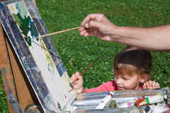 Easel artist in nature. Girl learns to paint with Royalty Free Stock Photos