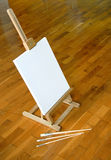 Easel with blank canvas. Easel with white canvas on brown parquet indoor Stock Photography