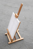 Easel with blank canvas. On gray concrete background Royalty Free Stock Photography