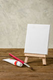 Easel with  blank canvas, paint and brush Royalty Free Stock Image