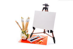 Easel with a blank canvas on a white background. Easel with a blank canvas, brush and paint Royalty Free Stock Photo