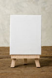 Easel with a blank canvas on a wooden background Stock Images