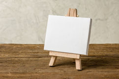 An easel with a blank canvas on a wooden background Royalty Free Stock Photos