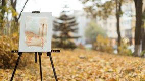 An easel with a finished picture standing in the autumn park, city and trees on background royalty free stock photography