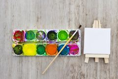 Easel, multicolors paint and brush for drawing. Creativity and painting concept.  stock photography