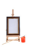 Easel, paint and small brush Stock Photos
