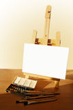 Easel with painting. Table easel with canvas, watercolor and brushes