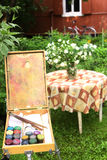 Easel with paints on the green garden background with jasmin bouquet i. N vase on the table on country house background Stock Image