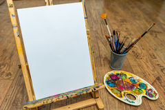 Easel palette and brushes with empty white canvas Stock Photo
