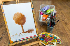 Easel with tree drawing with paint for art school. Learn to paint Stock Image