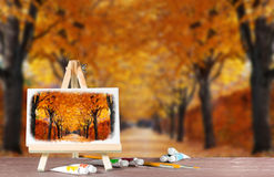 Easel with a watercolor painting of the autumn alley. Royalty Free Stock Images