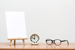 Easel on work desk. Wooden easel with blank canvas, round clock and glasses on table Stock Photos