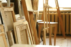 Easels and tablets made of light wood in art workshop. Photography of interior of art workshop. Main colors: ocher, beige. Foreground: tablets and easels Stock Images