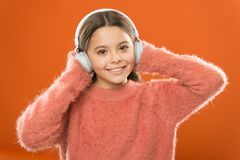 Easiest way to find new music similar to songs you already love. Girl cute little child wear headphones listen music. Kid listen music orange background stock photos