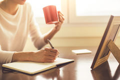 Easing into writing with cup of coffee Royalty Free Stock Image