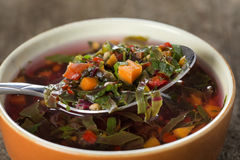 East Europe soup or red borscht in bowl with spoon over wood. Background royalty free stock photography