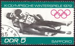East Germany circa 1972: Cancelled postage stamp printed in East Germany , that shows winter olympic bobsleigh competition in royalty free stock photos