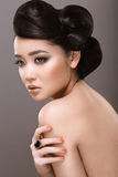East girl with unusual hairstyle. Beautiful woman oriental type with unusual hairstyle. Picture taken in the studio on a gray background Stock Photography