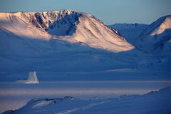 East Greenland winter landscape. Scoresbysund, dramatic East Greenland coastal landscape with iceberg frozen into pack ice Royalty Free Stock Images