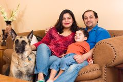 East Indian Family. An East-Indian couple site in their living room with their son and dog royalty free stock photography