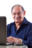 East Indian Man on Computer. Portrait of a smiling elderly East Indian businessman on his computer laptop Stock Image