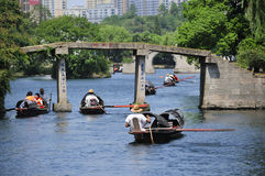 East Lake Shaoxing China. Chinese oarsmen sitting in the wu peng chuan or the black canopied boats on the canals of east lake dong Hu in the city of Shaoxing Royalty Free Stock Photo