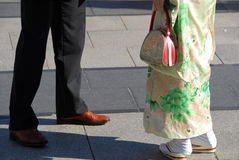 When east meets west. A chanced cross cultural encounter between East (woman in traditional Japanese kimono) and West (man in suit Stock Photo