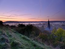 Early morning autumnal mist over East Meon village with Butser Hill and the South Downs in the background, South Downs National royalty free stock photos