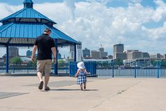 East Peoria, IL/USA - 05-27-2018: Walking along the riverfront on a summer day. East Peoria, IL/USA - 05-27-2018: Man and young granddaughter walking along the royalty free stock photos