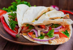 East pita bread with various fillings (meat, salami, egg, cucumber, parsley, tomato, chili pepper, Dijon mustard). Royalty Free Stock Photography