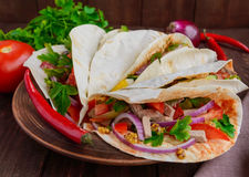 East pita bread with various fillings (meat, salami, egg, cucumber, parsley, tomato, chili pepper, Dijon mustard). Taco. Stock Image