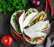 East pita bread with various fillings : meat, salami, egg, cucumber, parsley, tomato, chili pepper, Dijon mustard. Taco. Stock Photography