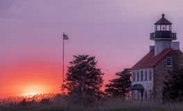East Point Lighthouse, New Jersey at sunset. East Point Lighthouse in New Jersey on the Delaware Bay as the sun begins to set and with US flag flying Stock Photography