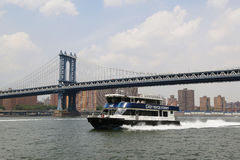 East River ferry boat rides under Manhattan Bridge Stock Photo