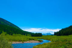 East River On Gothic Road. A winding river in a meadow, trees on either side, leading to a mountain peak royalty free stock photography