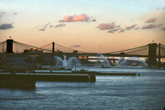 Three Bridges East River, New York City USA. Fire boats, helicopters, and bridges on New Yorks East River at dusk stock images