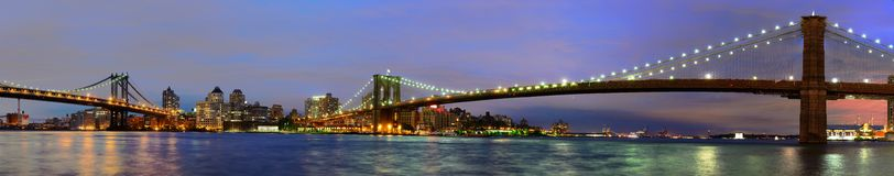 East River at Night in New York. Ultrawide angle of the Brooklyn Bridge and Manhattan Bridge spanning the East River towards Brooklyn in New York City Royalty Free Stock Images