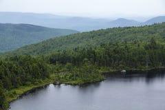 East shore Lake Solitude, south side, Mt. Sunapee, New Hampshire. East shore of Lake Solitude on the south slopes of Mt. Sunapee, New Hampshire, on a hazy royalty free stock image