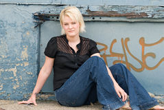 East Side Girl. Serious blond girl sitting on ground in front of graffiti Royalty Free Stock Photo