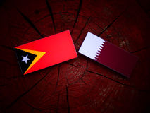 East Timorese flag with Qatari flag on a tree stump isolated. East Timorese flag with Qatari flag on a tree stump Royalty Free Stock Photos