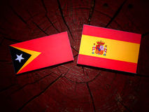 East Timorese flag with Spanish flag on a tree stump royalty free stock images