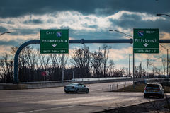 East West Pennsylvania Turnpike sign. Harrisburg, PA - January 1, 2017: At the Pennsylvania Turnpike entrance, large directional signs for east or west travel Royalty Free Stock Photography