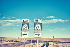 East or West, retro toned photo of road signs. East or West, retro toned photo of road signs at sunset, choice and travel concept royalty free stock images
