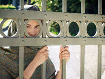 East woman. Hiding behind the grid looking straight Royalty Free Stock Image