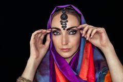 East woman in burqa with jewels on a black background. stock photography