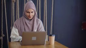 East woman working from cafe. Lovely smiling arabic woman working on laptop in cafe and drinking coffee. Muslim woman on freelance. Happy east woman in hijab stock video footage