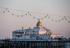 Eastbourne pier in the evening. Fantastic eastbourne pier in southengland in the evening, sun is going own and lights the building, silent ocean royalty free stock photo