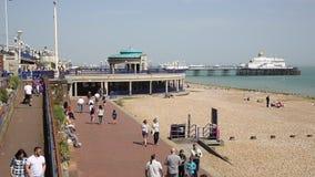 Eastbourne East Sussex Inglaterra Reino Unido com os povos que apreciam a luz do sol da mola que anda no passeio da frente maríti vídeos de arquivo