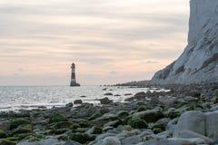 19/09/2018 Eastbourne, het Verenigd Koninkrijk Kiezelachtige Hoofdvuurtoren in het overzees en de zonsondergang op de achtergrond stock fotografie